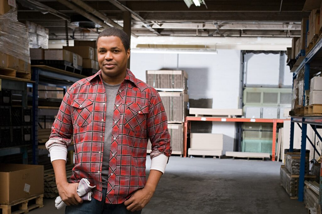 Man in Warehouse wearing flannel shirt with hands in pocket