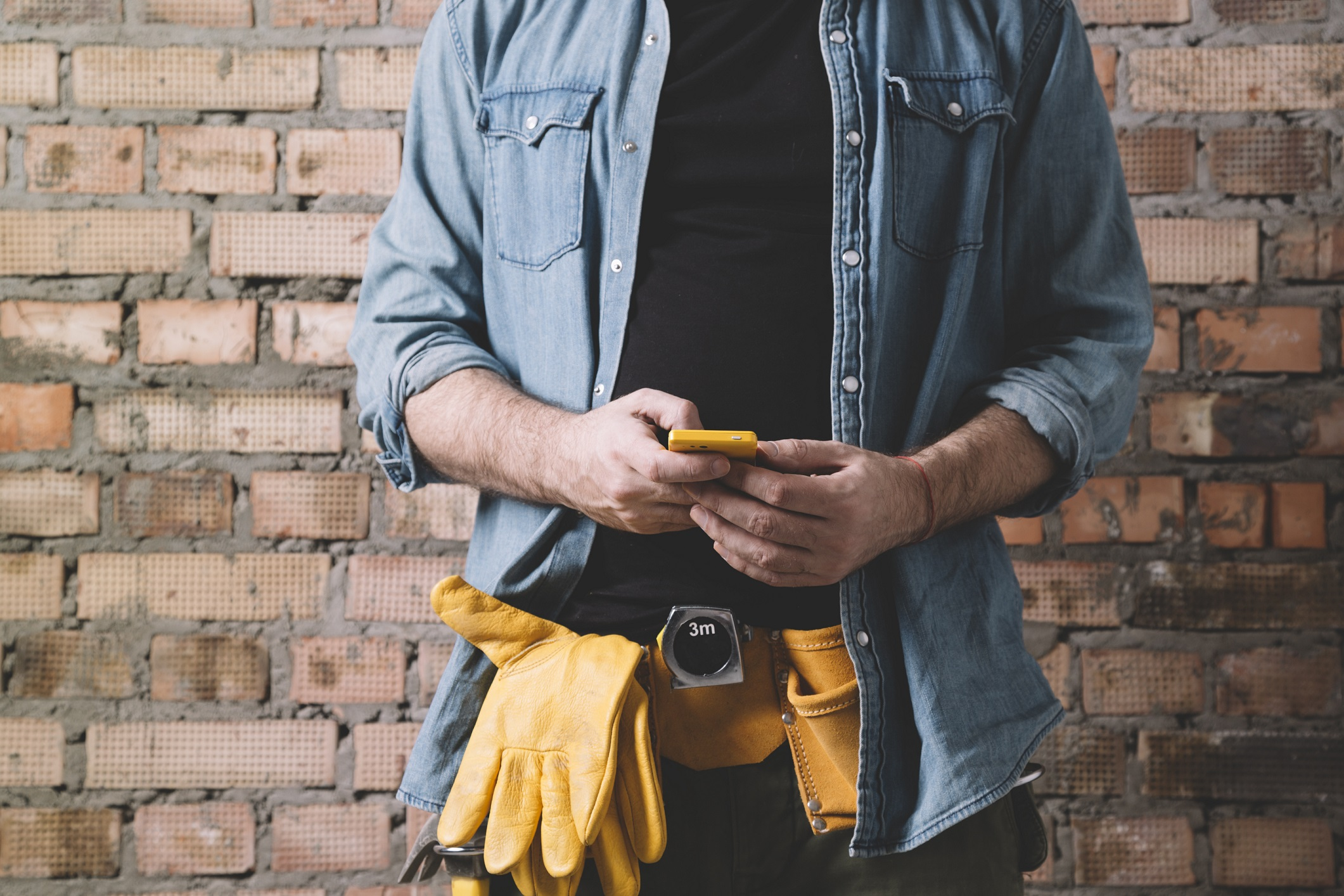 Construction worker texting on phone