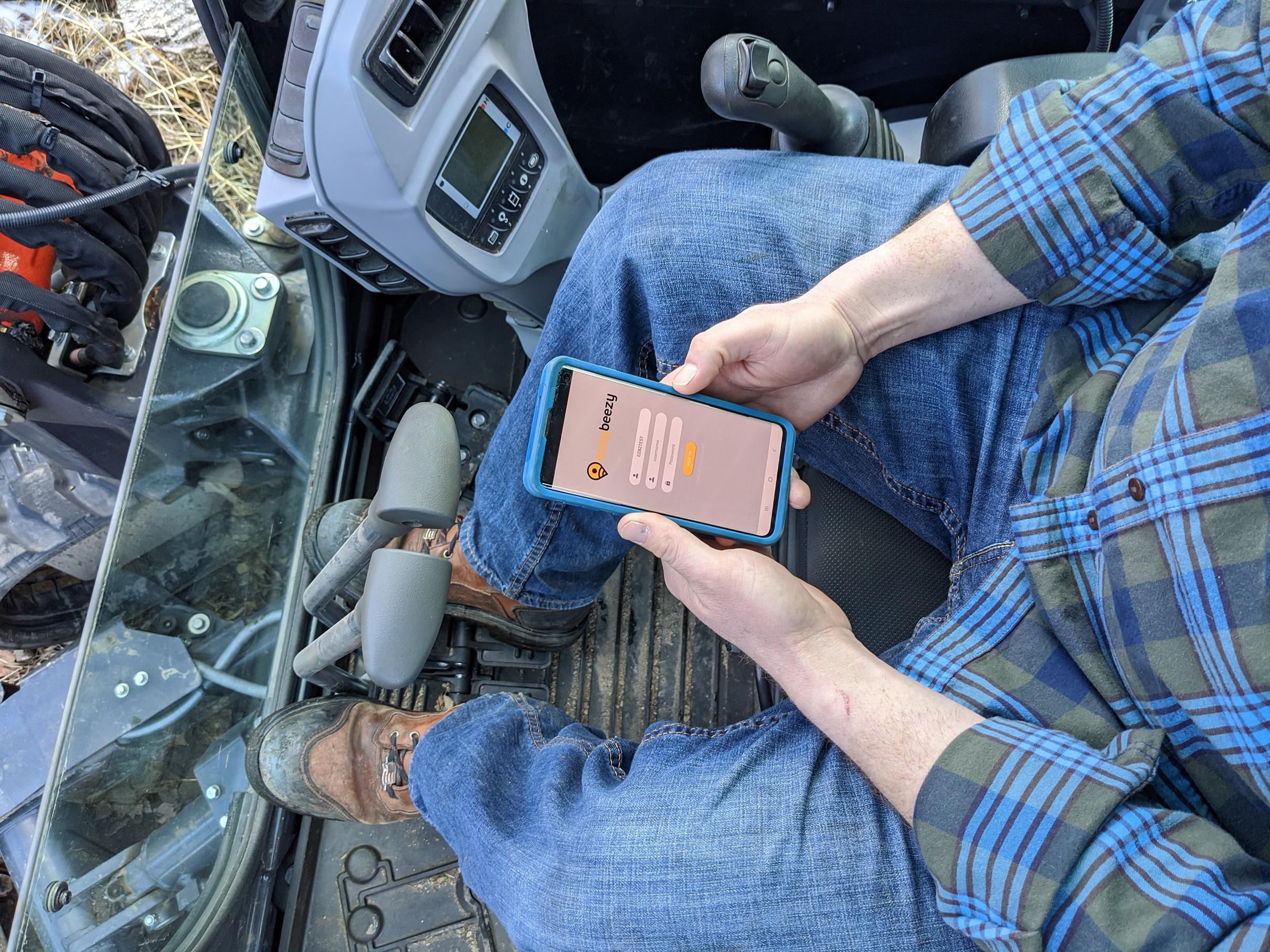 Man in flannel shirt on EZBZ app in excavator